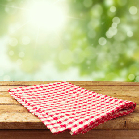 picnic cloth: Empty wooden deck table with tablecloth over bokeh background