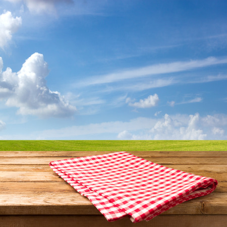 warm cloth: Empty table with tablecloth over beautiful meadow and blue sky