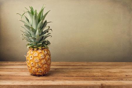 クランジ背景に木製のテーブル上にパイナップル 写真素材