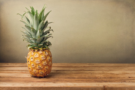 Pineapple on wooden table over crunge background