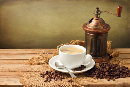 Vintage coffee grinder and coffee cup over wooden background over grunge background