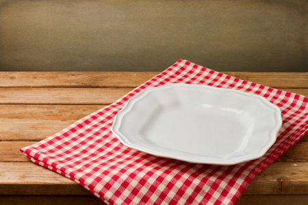 empty space: Empty white plate on tablecloth on wooden vintage table