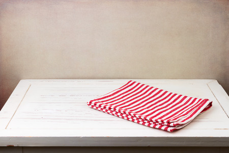 Background with white wooden table and red striped tablecloth Stockfoto