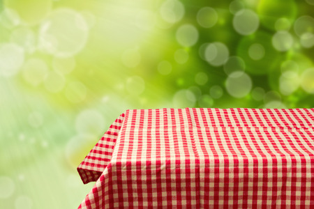 picnic cloth: Empty table with red checked tablecloth over green bokeh background Stock Photo