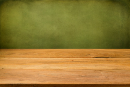 Empty wooden table over grunge green background Stockfoto