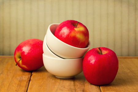 Red apple in stack of bowls on wooden table over vintage wallpaper photo