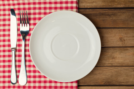 Empty plate with fork and knife on tablecloth over wooden background