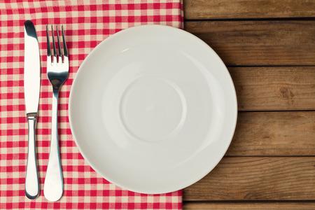 manteles: Plato vac�o con tenedor y cuchillo sobre mantel sobre fondo de madera Foto de archivo