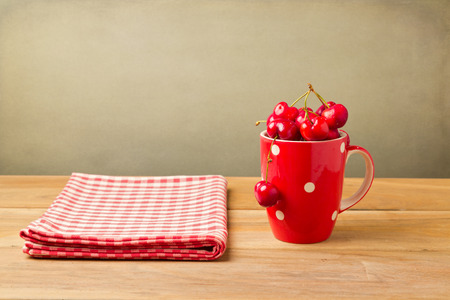 Cherries in red cup with tablecloth on wooden table photo