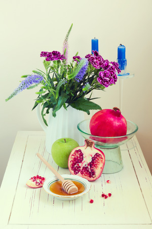 honey apple: Honey, apple, pomegranate and flowers on wooden white table Stock Photo