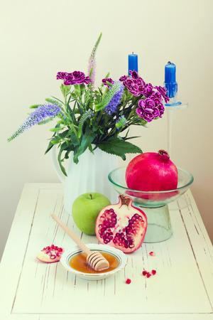 honey apple: Honey, apple, pomegranate and flowers on wooden white table Stock Photo