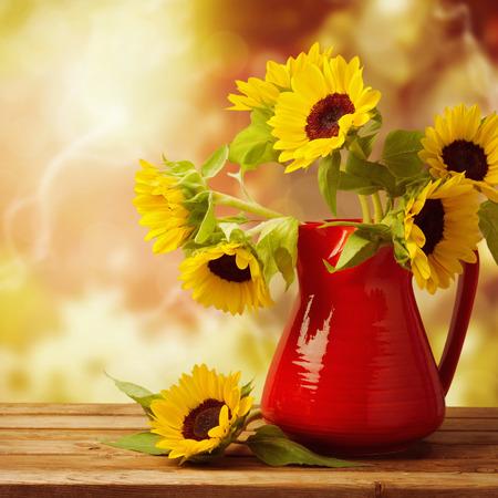 Zonnebloem boeket in rode kruik op houten tafel over mooie herfst bokeh achtergrond Stockfoto