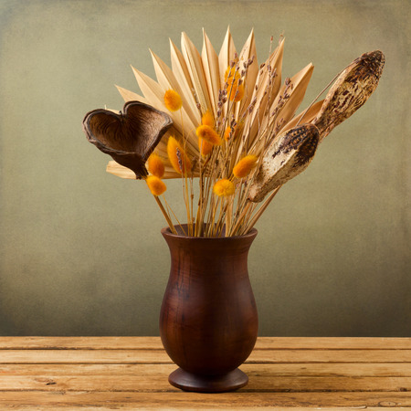dried leaf: Tropical dried flowers in wooden vase over grunge background