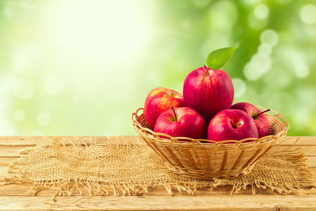 정원 나뭇잎 배경 위에 나무 테이블에 바구니에 사과