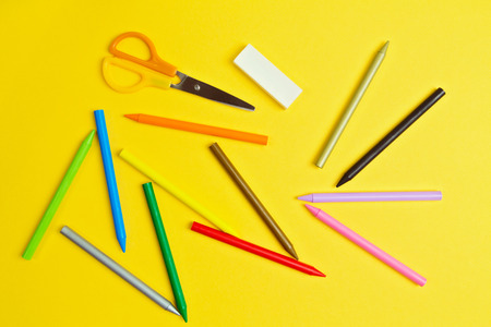 yelloow: Color pencils and scissors on yelloow paper background