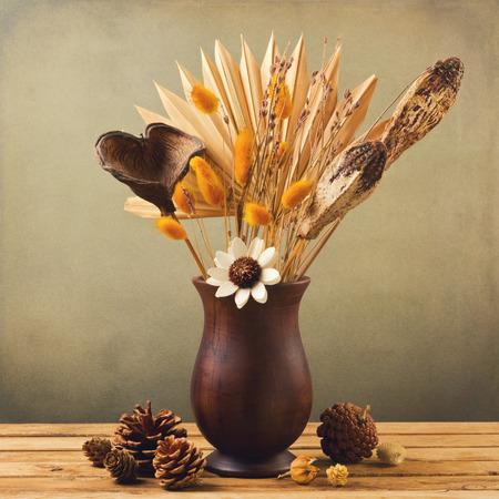 flores secas: Flores secadas en florero de madera con pinecorn sobre el fondo del grunge Foto de archivo