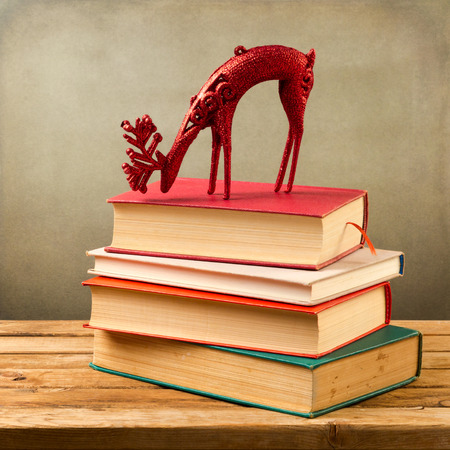 sceince: Old books and Christmas deer on wooden table