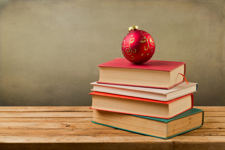 sceince: Vintage books with Christmas ornament bauble on wooden table over grunge background