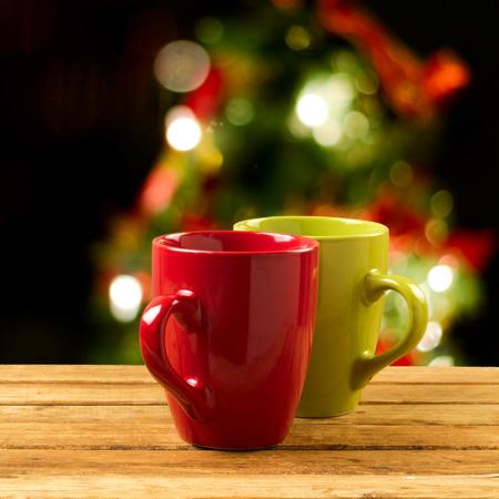 Christmas holiday mugs on wooden table over Christmas tree bokeh background photo