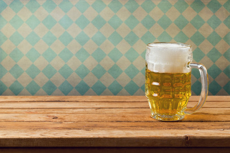 interior wallpaper: Oktoberfest holiday. Beer on wooden table over retro wallpaper with bavarian flag pattern