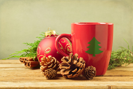 Christmas mug with pine corns and ornaments on wooden table photo