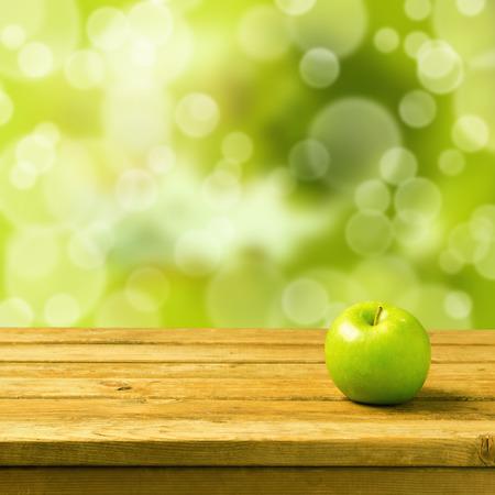manzana verde: Manzana verde en mesa de madera de la vendimia sobre fondo de bokeh