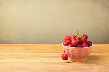 Bowl full of cherries on wooden table over grunge background photo