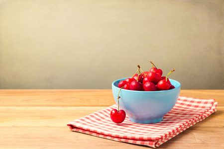 Bowl full of cherries on tablecloth on wooden table over grunge background photo