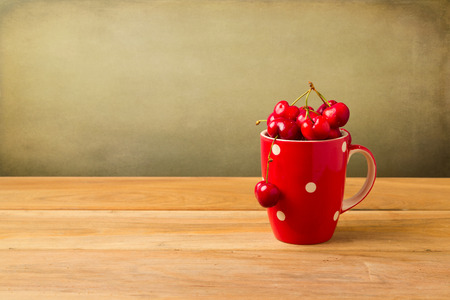 Red mug full of cherries on wooden table over grunge background photo