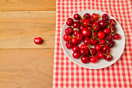 Cherries on plate with tablecloth on wooden background photo