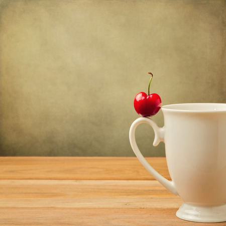 Single cherry on cup handle over grunge background photo