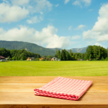 red mountain open space: Empty table covered with checked tablecloth over beautiful landscape Stock Photo