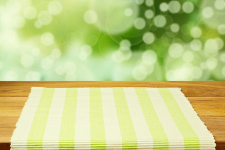 Empty wooden table with tablecloth over bokeh background photo