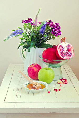 apple and honey: Still life with apple, honey, pomegranate and flowers on wooden white table