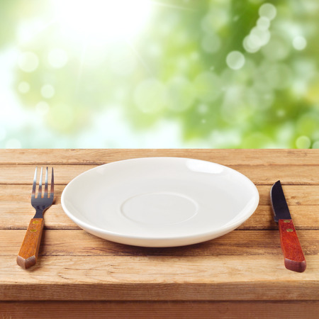plate setting: Empty plate with knife and fork on wooden table over garden bokeh background Stock Photo