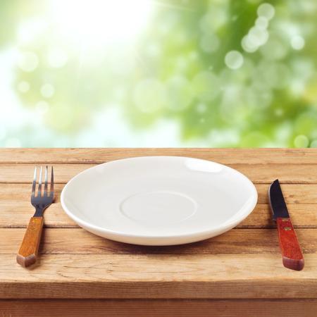 Lege plaat met mes en vork op houten tafel over de tuin bokeh achtergrond Stockfoto