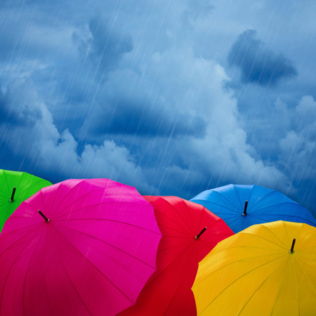 rainy day: Colorful umbrellas over cloudy sky Stock Photo