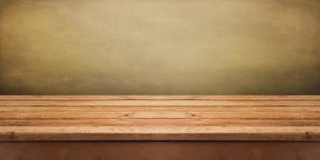 Fondo con la mesa cubierta de madera vacía sobre papel pintado del grunge