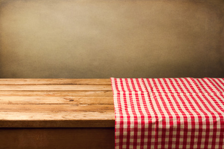 tablecloth: Empty wooden table covered with red checked tablecloth