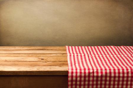 tabla de madera: Mesa de madera vac�a cubierta con mantel controlado rojo Foto de archivo