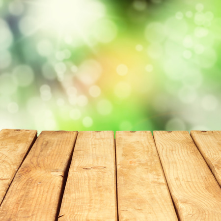 Wooden deck table over beautiful bokeh background Imagens