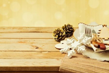 golden christmas: Christmas table setting with plate, fork and knife ornaments on wooden table Stock Photo