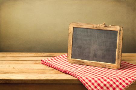 グランジ背景に木製のテーブルのテーブル クロスの上のレトロな黒板