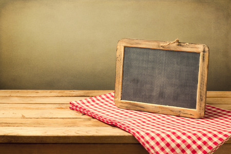 red kitchen: Retro chalkboard on tablecloth on wooden table over grunge background