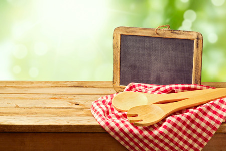 checked fabric: Cooking and backing background with wooden table and chalkboard over green bokeh