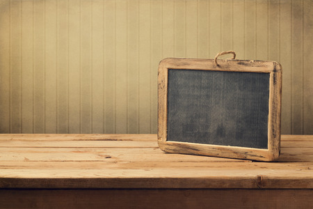 Vintage background with chalkboard on wooden table over retro wallpaper