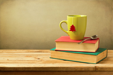 books on a wooden surface: Christmas tea cup on stack of books on wooden table