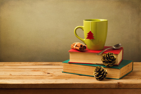 Christmas tea mug on books on wooden table over grunge background with copy space