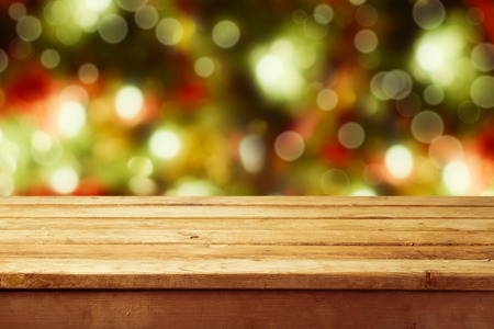 Christmas holiday background with empty wooden deck table over festive bokeh