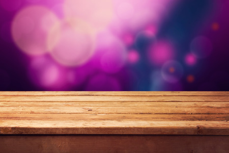 empty table: Christmas background with empty wooden table and purple bokeh